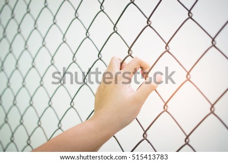 Women holding hands on the background of metal mesh fence
