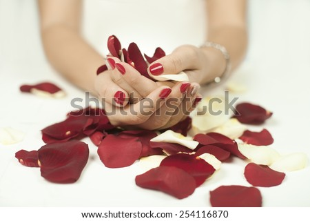 Women holding red and white petals on a white background - stock photo