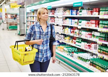Women housewife with yellow basket shopping in supermarket - stock photo