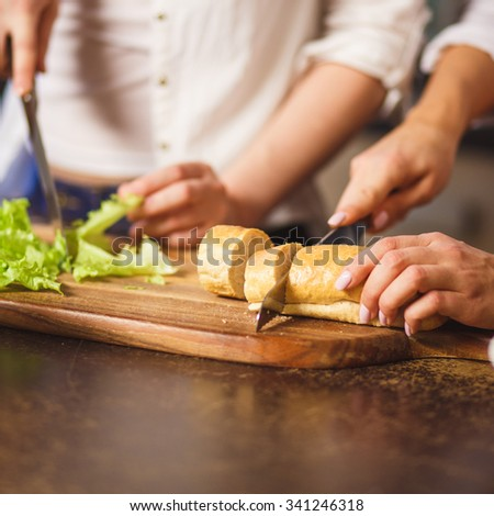 women housewifes preparing lettuce and bread on cutting board in kitchen, close up photo soft focus