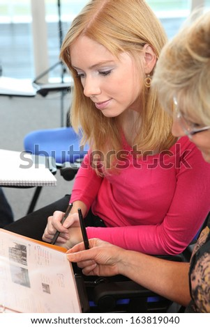 Women in an office looking at a brochure - stock photo