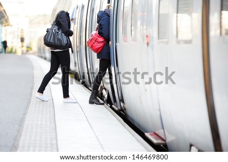 Women in hurry enters train - stock photo