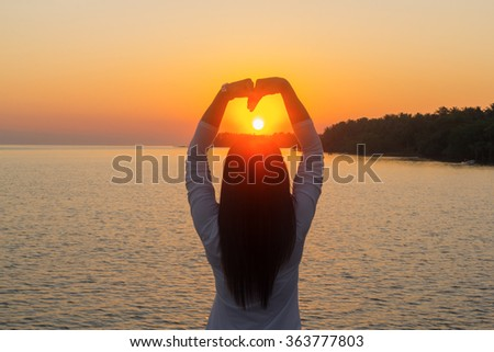 women in love ,Hands make heart at sunset