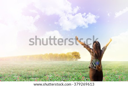women in lovely mini pink and yellow flower sun plant or pursley and fresh colourful dreamy sky with line of trees, concept of freedom and cheerful on nature garden background