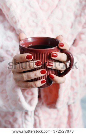 Women in pink bathrobe holds mug with coffee in hands
