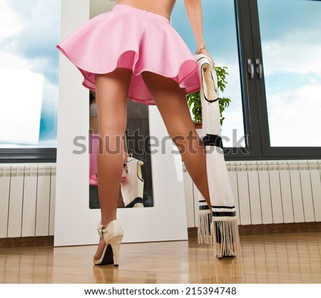women in pink mini skirt and high heels in front of mirror choosing dress - stock photo