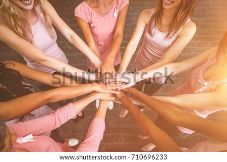 Women in pink outfits joining in a circle for breast cancer awareness against a dark wall