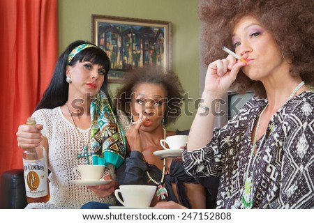 Women in 1960s clothing smoking cigarettes and drinking whiskey - stock photo