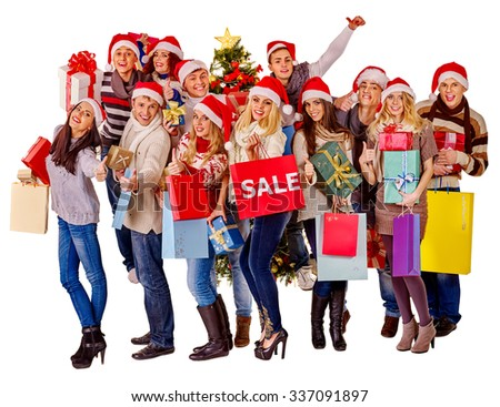 Women in Santa hat holding sign saying sale and shopping bags.