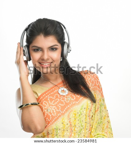 Women in sari hearing to music with head phones - stock photo
