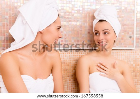 Women in sauna. Two beautiful young women wrapped in towel talking to each other and smiling while relaxing in sauna - stock photo