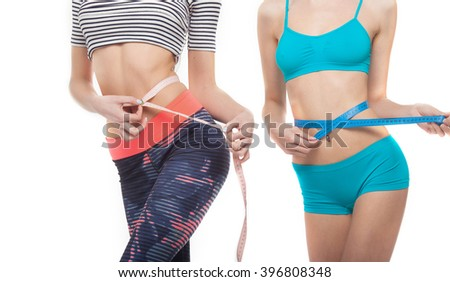 Women in sport with tape measures isolated on a white background. Slim body.  - stock photo