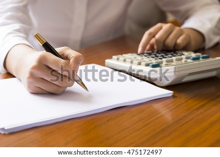 Women in the office table, while the use of calculators, while holding pen on paper records
