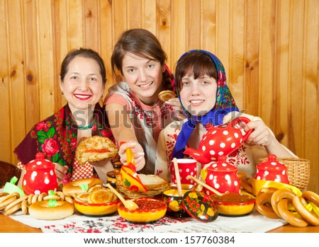 Women in traditional  clothes eating pancake during  Shrovetide