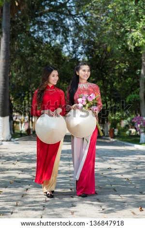 Women in traditional red dresses walking in the park