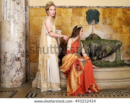women in traditional roman clothing posing in temple