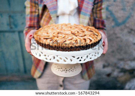 Women in vintage clothes holding apple pie - stock photo