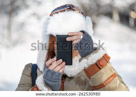 Women in winter clothing, fingerless mittens and ornamented hat with white fur photographing snowy landscape by a mobile phone. Shallow dof. Focus on hands. - stock photo