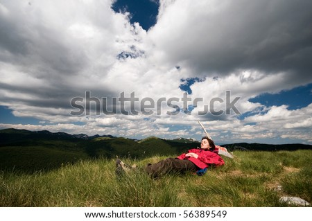 Women is laying down on the grass on top of mountain peek, relaxing from everyday's troubles with dramatic clouds over her head - stock photo