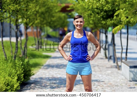 Women jogger in park smiling.