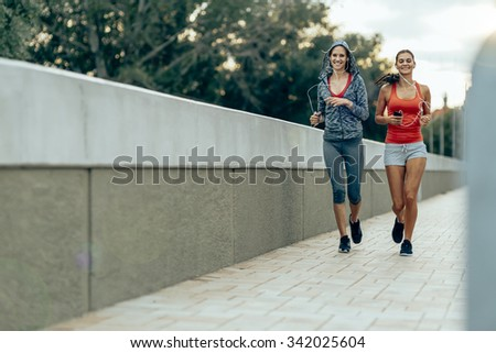 Women jogging in city in dusk and improving their stamina while losing weight - stock photo