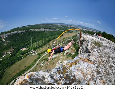 Women jump off a cliff.Crimea. Kachy-Kalion. - stock photo