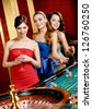 Women keeping glasses of spirits play roulette at the gambling house - stock photo