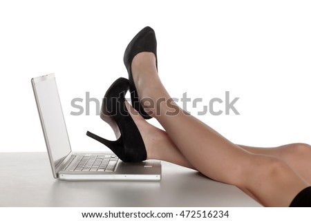 women legs in shoes on a laptop on the table