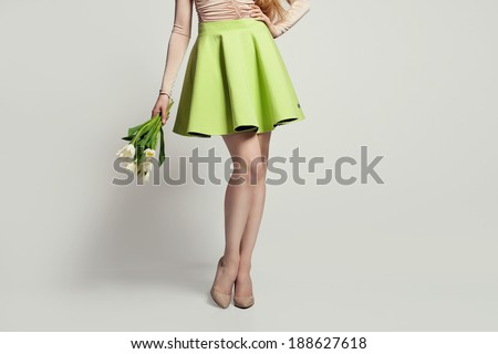 women legs with nude shoes, skirt and flowers - stock photo