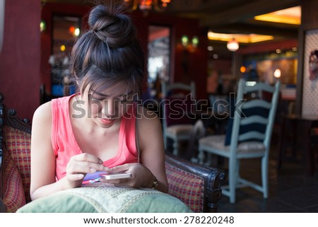 women lifestyle using a mobile phone in cafe coffee shop with texting message on app smartphone playing social network - stock photo