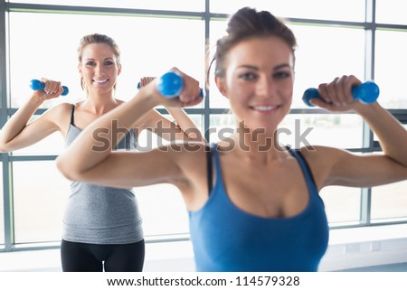 Women lifting weights in gym - stock photo