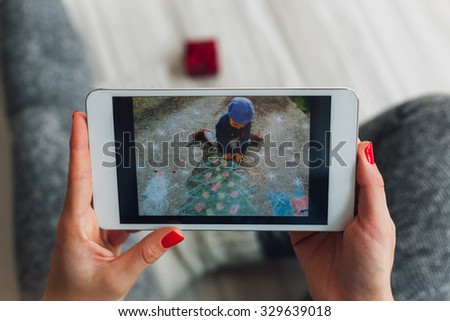 Women looking Christmas ideas on a tablet. Photo on the tablet is the property of Kikovic and can be licensed at Shutterstock.com. - stock photo