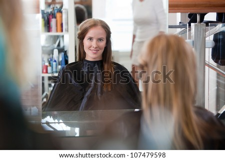 Women looking in mirror at beauty salon.