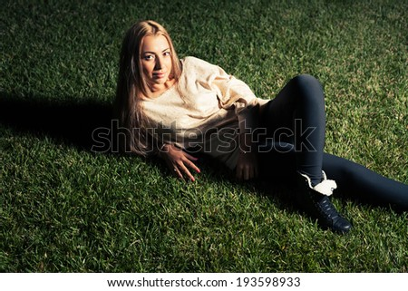 Women lying on a green grass and looking at camera with pretty smile
