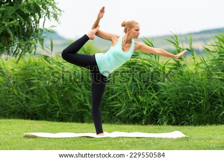 Women make yoga in nature on the green grass, Natarajasana, Lord of the Dance Pose - stock photo