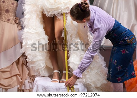 Women making adjustment to wedding gown in professional fashion designer studio - stock photo