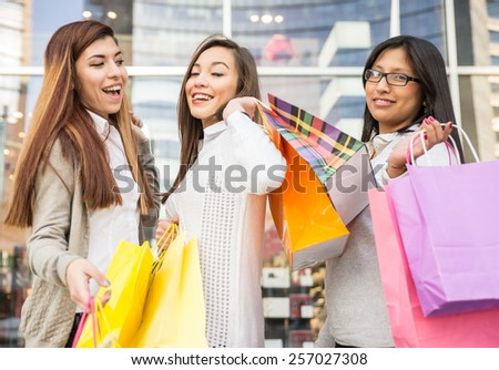 Women of diverse ethnics with shopping bags - Portrait of three pretty girls walking and looking at shops - stock photo