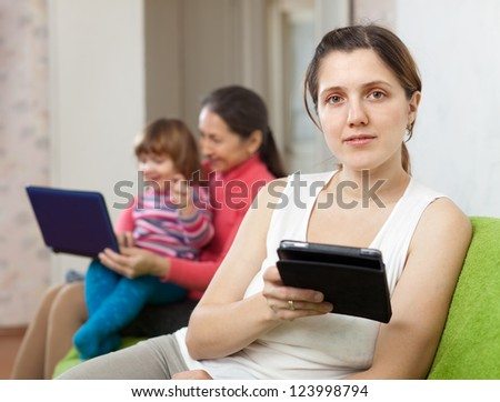 women of three generations sits on the sofa with electronic devices - stock photo