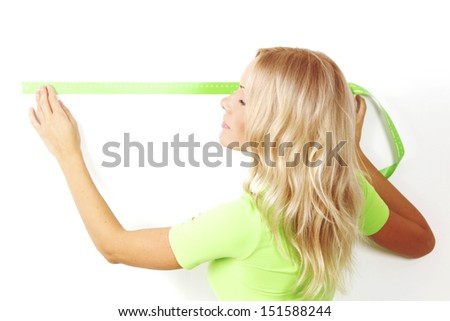 women often with a measuring tape to the wall - stock photo
