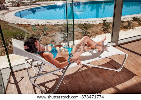 Women on a sun lounger beside the indoor pool - stock photo