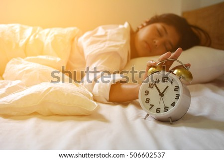 Women on bed at morning with alarm clock ,focus of alarm clock ,vintage tone