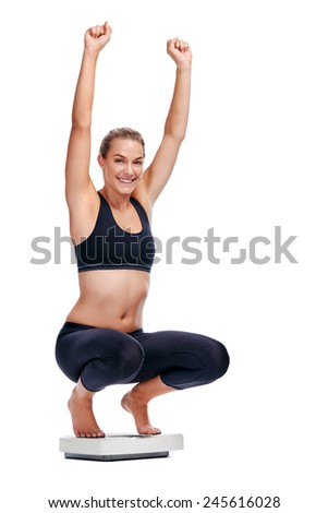 Women on scale cheering for achieving her weight loss goal isolated on white background - stock photo