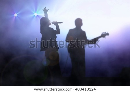 Women on stage singing with guitarist under spotlight - stock photo