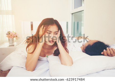 Women on symptoms of insomnia. Use earmuffs to prevent snoring boyfriend. Loud snoring beside the bed. , The concept of snoring ,insomnia and respiratory system.