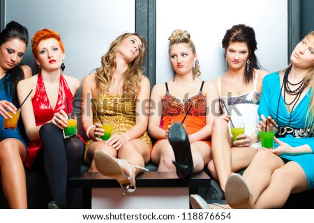 Women or models in club or disco drinking cocktails having no fun as the party is boring - stock photo