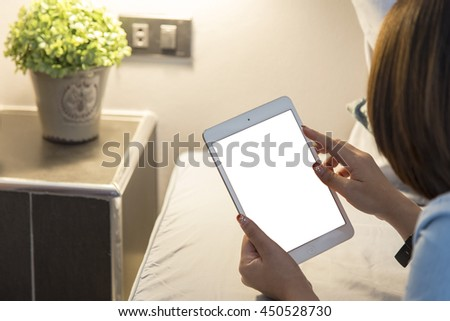 Women playing a tablet one the bed and selective focus.
