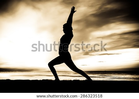 women playing yoga at beach side