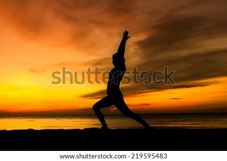 women playing yoga at beach side on sunset