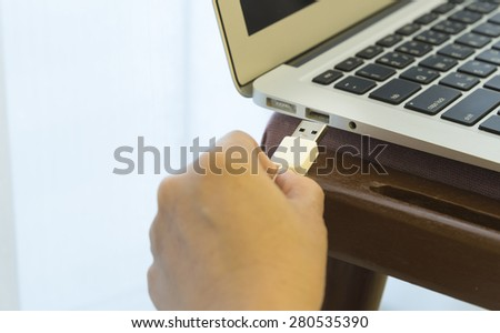 Women plug external devices to the laptop with her.