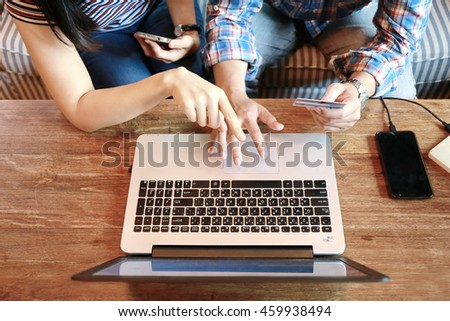 women pointing laptop screen and man typing laptop and hold credit card on wood table, internet of things.People touching on phones while discussion and shopping online by credit card,personal loans.